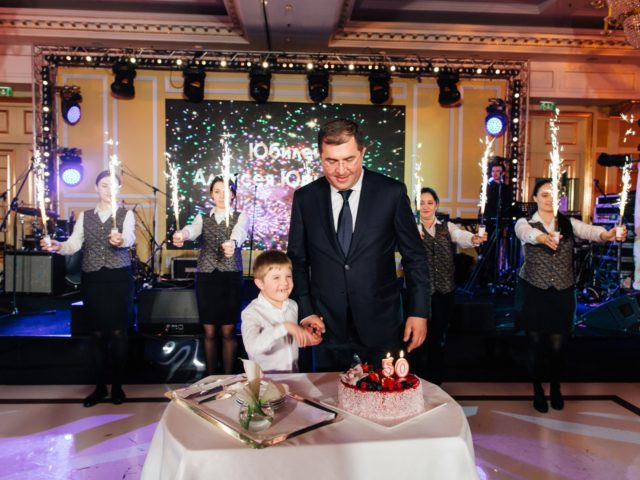 Юбиляр готовится задуть свечи на торте