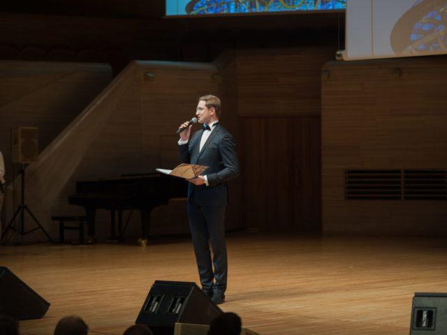 Ведущий Юбилея компании Роман Акимов на сцене Светлановского Зала Дома Музыки